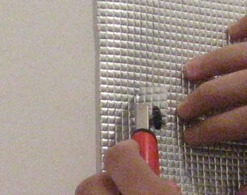 Ajustam folia reflectorizanta cu cutterul in jurul diblurilor de fixare a caloriferului