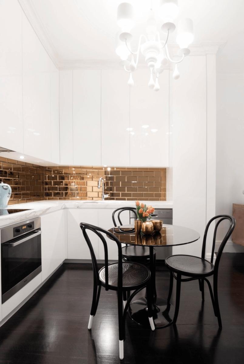 Bucatarie cu mobilier alb si perete placat cu faianta aurie tip zidarie si pardoseala din parchet laminat negru