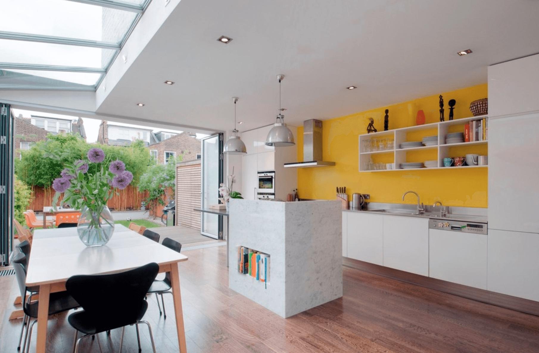 Bucatarie openspace cu mobilier alb si perete galben