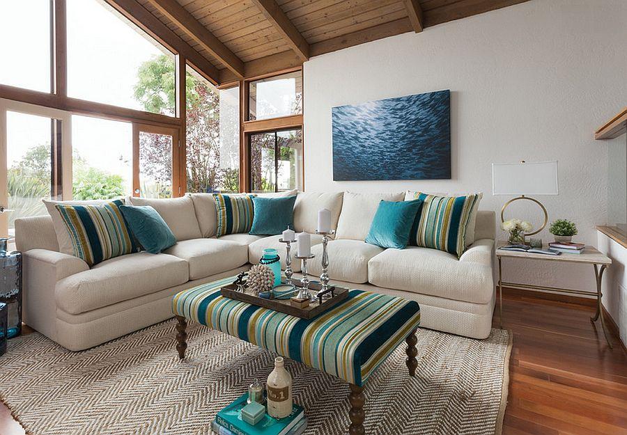 Canapea de colt alba cu masa si perne decoratice cu imprimeu in dungi turcoaz