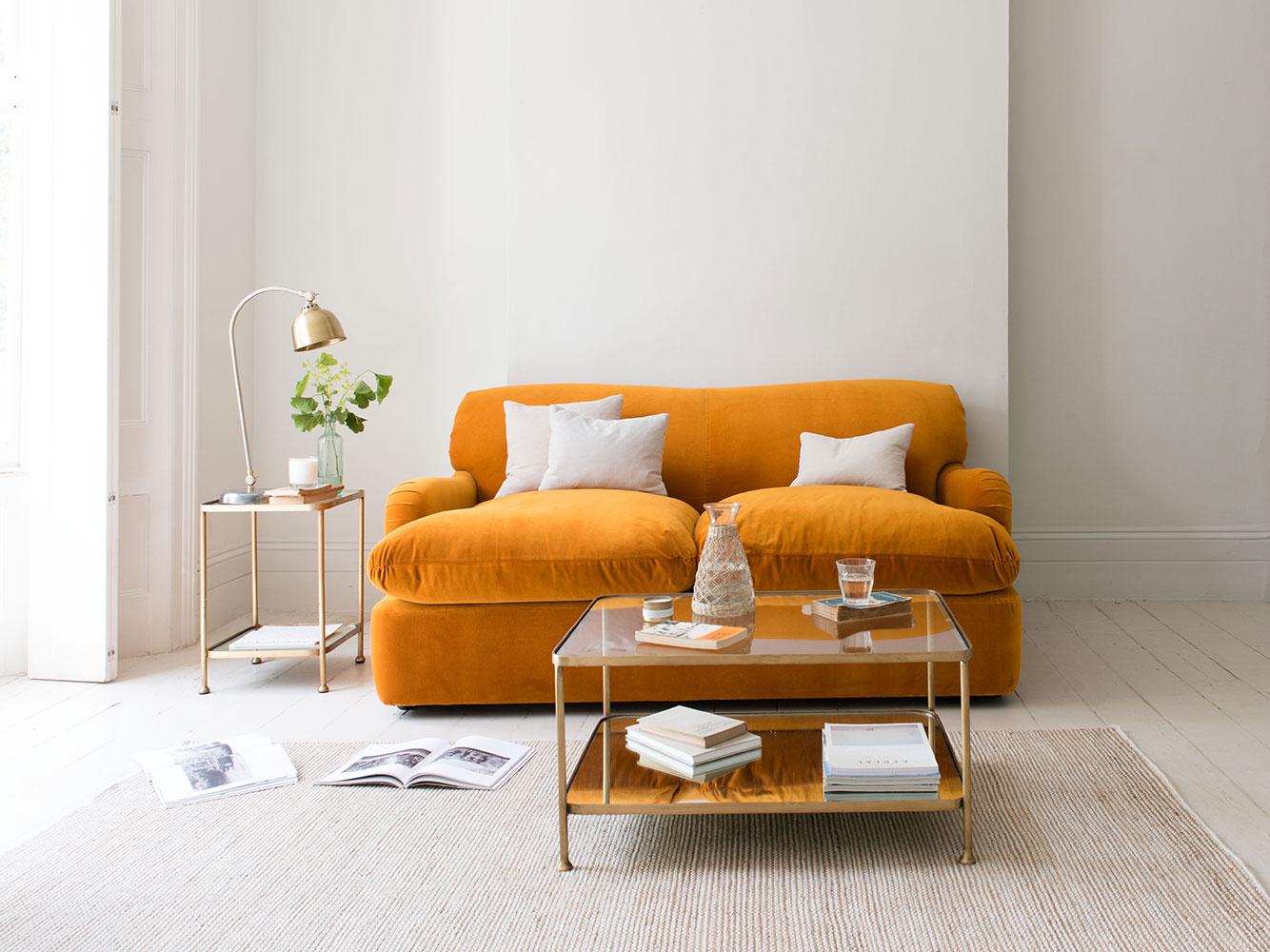 Canapea portocalie cu masa aurie cu blaturi din sticla