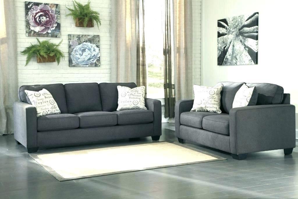 Canapele gri cu perne decorative albe si covor alb in living cu pereti din caramida aparenta alba