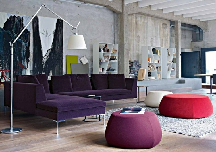 Living in stil industrial cu canapea mov inchis si taburete colorate