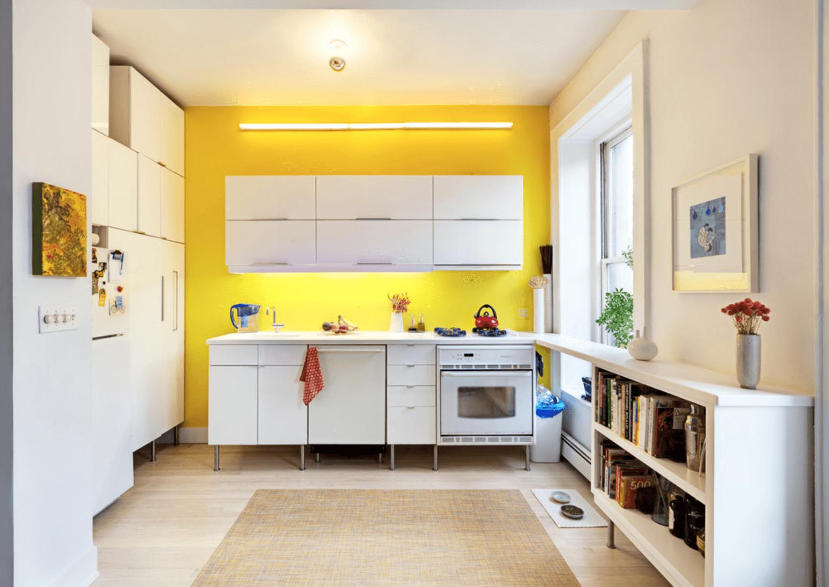 Perete galben in bucatarie cu mobilier alb