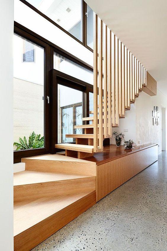Scara din lemn facuta din doua parti primele trepte balansate cu suport cu depozitare si restul scarii cu vang central si trepte din lemn cu riflaj vertical despartitor