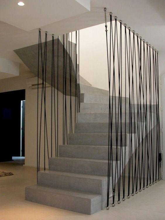 Scara gri din beton balansata cu intoarcere 180 si parapet din cavluri metalic eintinse prinse in podea si tavan