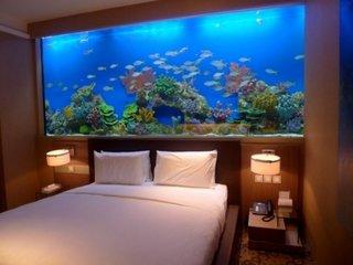 Dormitor opulent cu acvariu pe peretele de deasupra patului