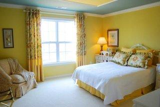 Dormitor cu draperie galbena cu model floral