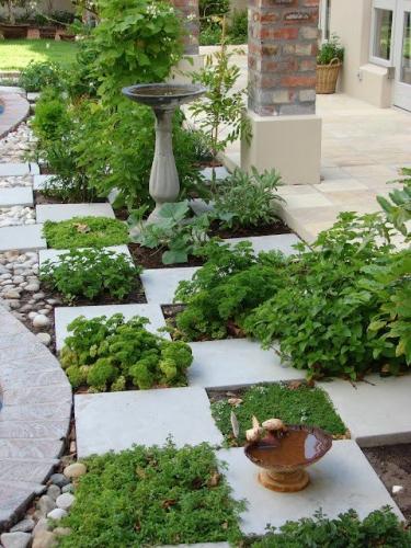 Tabla de sah facuta din dale de piatra si plante verzi