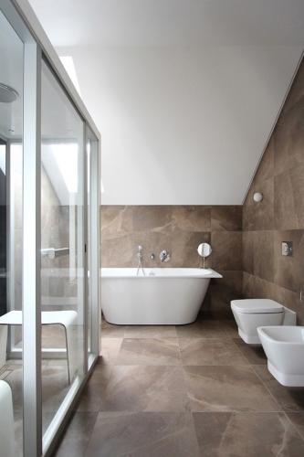 Baie mare placata cu placi de ceramica in nuante neutre si vas de toaleta si bideu suspendate