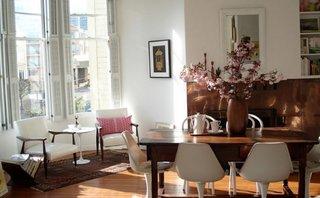Living amenajat cu dining in stil boho chic cu masa din lemn si scaune moderne albe
