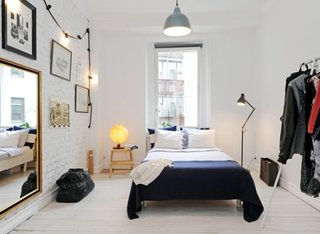 Dormitor cu pat amplasat in fata ferestrei si oglinda mare pe perete