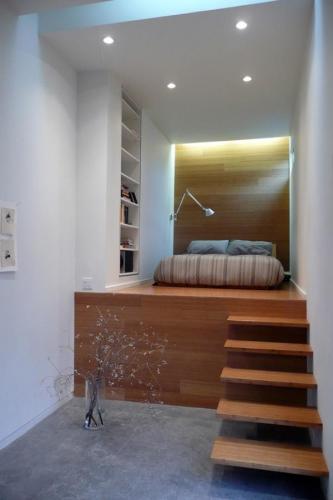 Dormitor cu pat amplasat pe o platforma din lemn cu scara