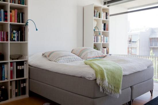 Dormitor cu pat pe mijloc si doua corpuri inalte cu rafturi