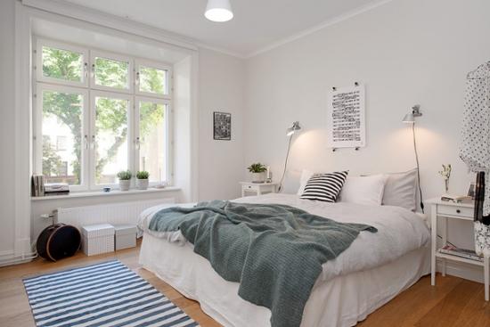 Dormitor mic alb cu pat pe mijloc si covor alb cu dungi bleumarin