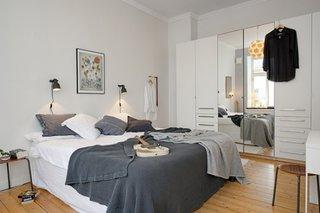 Dormitor mic alb cu veioze deasupra patului de culoare gri