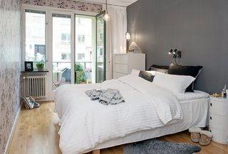 Dormitor mic cu peretele din spatele patului gri inchis si pereti cu tapet