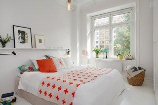 Dormitor mic de apartament zugravit in alb si cuvertura si perne portocalii