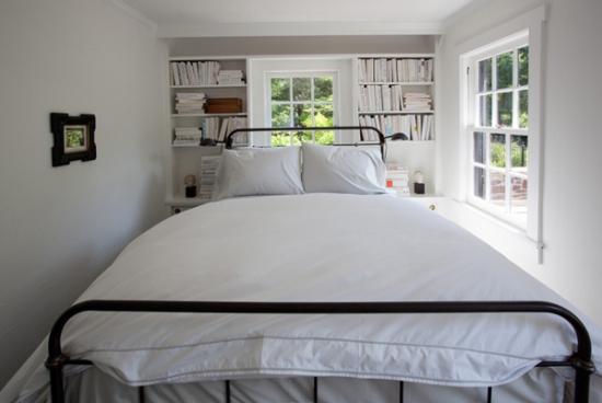 Dormitor mic si ingust cu pat pe mijloc si noptiere cu etajere cu carti deasupra