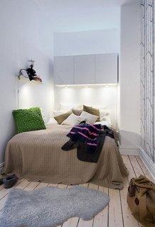 Pat in dormitor cu corpuri suspendate deasupra si spoturi incastrate