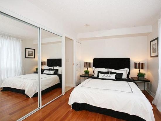 Pat negru si dressign cu oglinzi intr-un mic dormitor