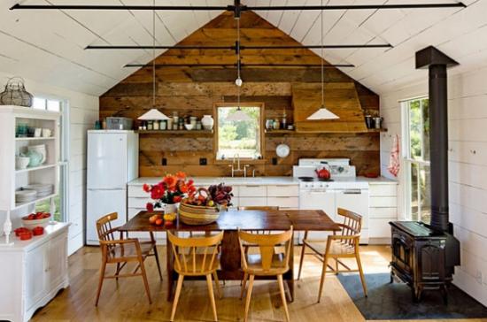 Bucatarie cu perete placat cu lemn si masa si scaune din lemn