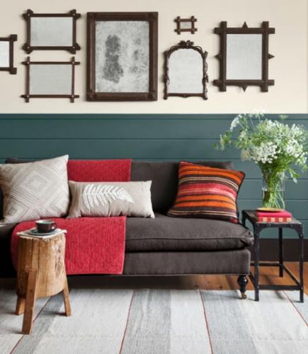 Canapea fixa de doua locuri si perne decorative colorate si colectie de rame pe perete