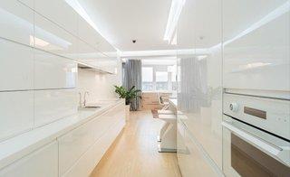 Bucatarie lunga si ingusta cu mobilier alb pe ambii pereti