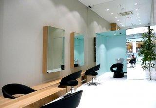 Zona de coafor amenajata cu scaune negre rotative din piele si oglinzi mari