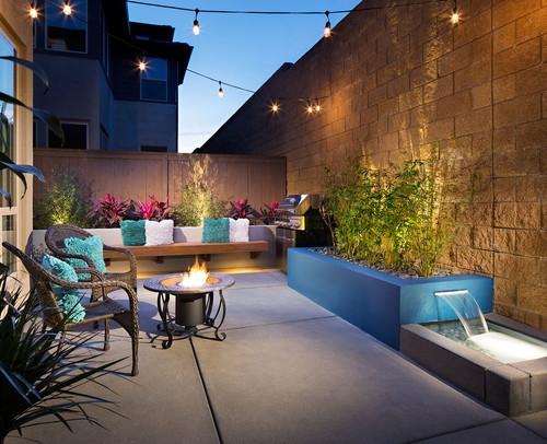 Terasa mica cu dale mari de beton fantana arteziana si canapea de ciment decorata cu perne colorate