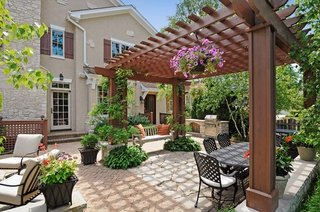 terasa placata cu dale si pergola decorata cu plante decorative