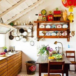Bucatarie rustica cu rafturi si etajere si masa din lemn