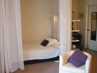 Zona de dormit cu pat cu perdea semitransparenta