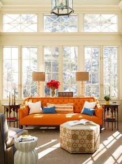 Living cu ferestre mari cu rama alba si canapea portocalie