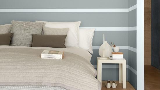 Perete din spatele patului zugravit in gri cu dungi orizontale albe