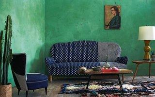 Living cu pereti verzi si canapea si fotolii patchwork cu tonuri albastre