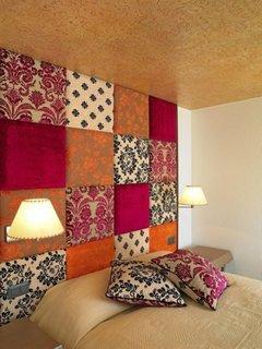 Perete din dormitor tapitat cu petice de materiale