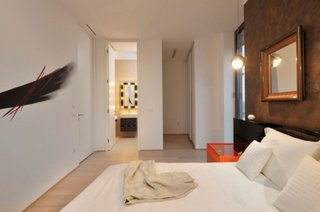 Dormitor matrimonial cu perete in nuante de bronz