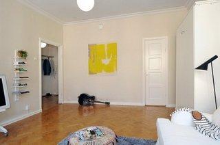 Living cu mobila alba pereti crem si tablou cu galben aprins