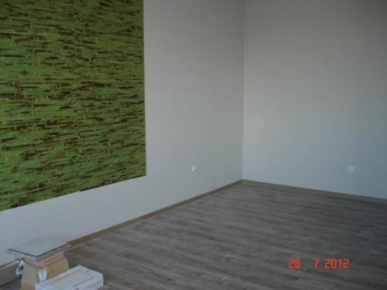 Living cu pereti albi si perete cu panou verde din bambus