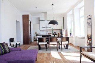 Studio de dimensiuni mai mari cu mobila alba si canapea violet