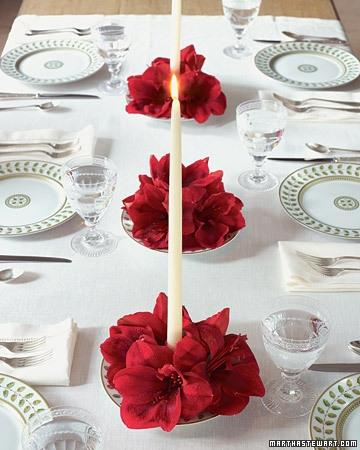 Masa aranjata cu fata de masa si farfurii albe si aranjamente florale rosii cu lumanari albe