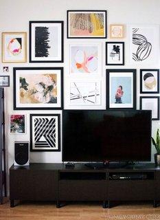 Comoda maro joasa cu televizor inconjurat de tablouri