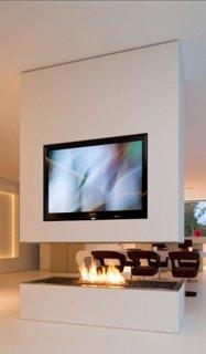 Living alb cu televizor mare pe perete deasupra semineului