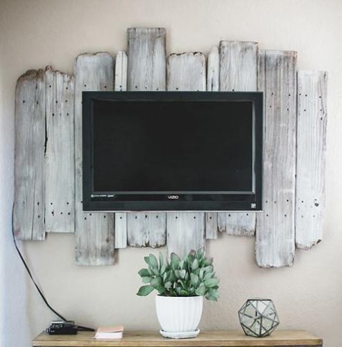 Televizor montat pe perete pe scanduri de lemn