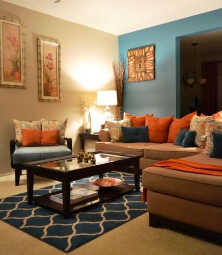 Living cu canapea maro si decoratiuni albastre si portocalii