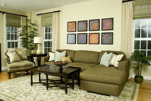 Canapea coltar din stofa verde cu masuta de cafea maro inchis covor stil persan si jaluzele din paie