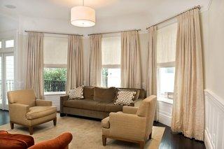 Culori neutre pentru amenajarea unui living cu canapea maro fotolii crem si jaluzele si perdele crem