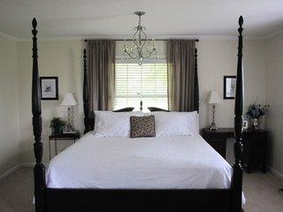 Dormitor mic amenajat cu pat pe mijloc si jaluzele albe cu perdele crem inchis