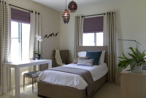 Dormitor mic cu pat pe mijloc si birou si cu draperii cu model la fereastra